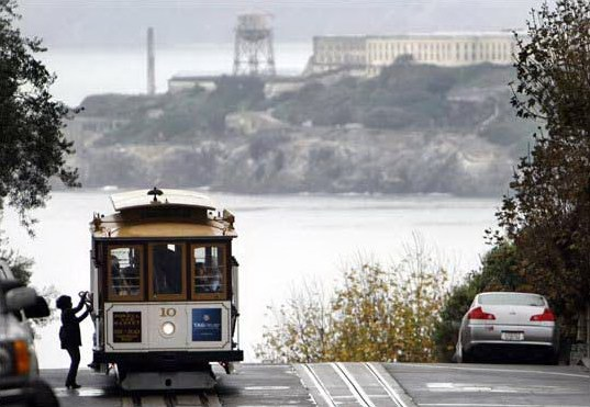 An emission-free San Francisco cable car makes a stop on Russian Hill, with Alcatraz Island in the background.